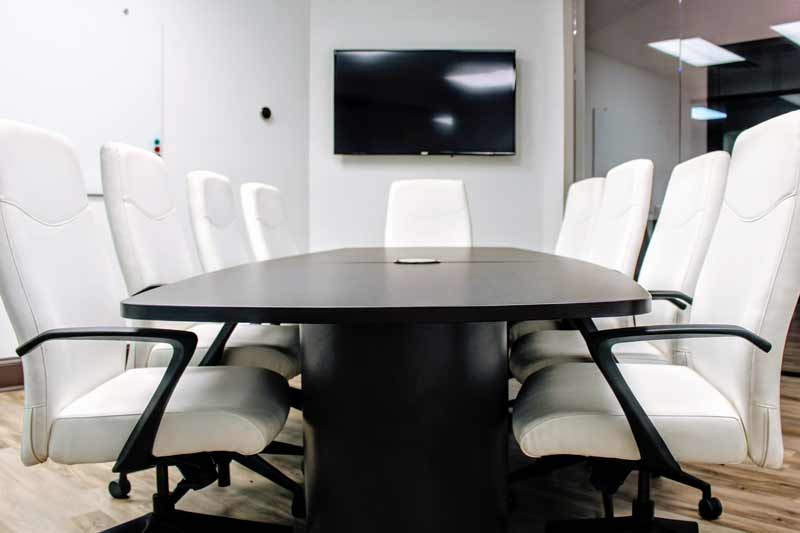 Atlanta Exec Suite's conference room with an oak table and 8 black leather executive chairs.  Additional seats along the wall can be brought to the table.