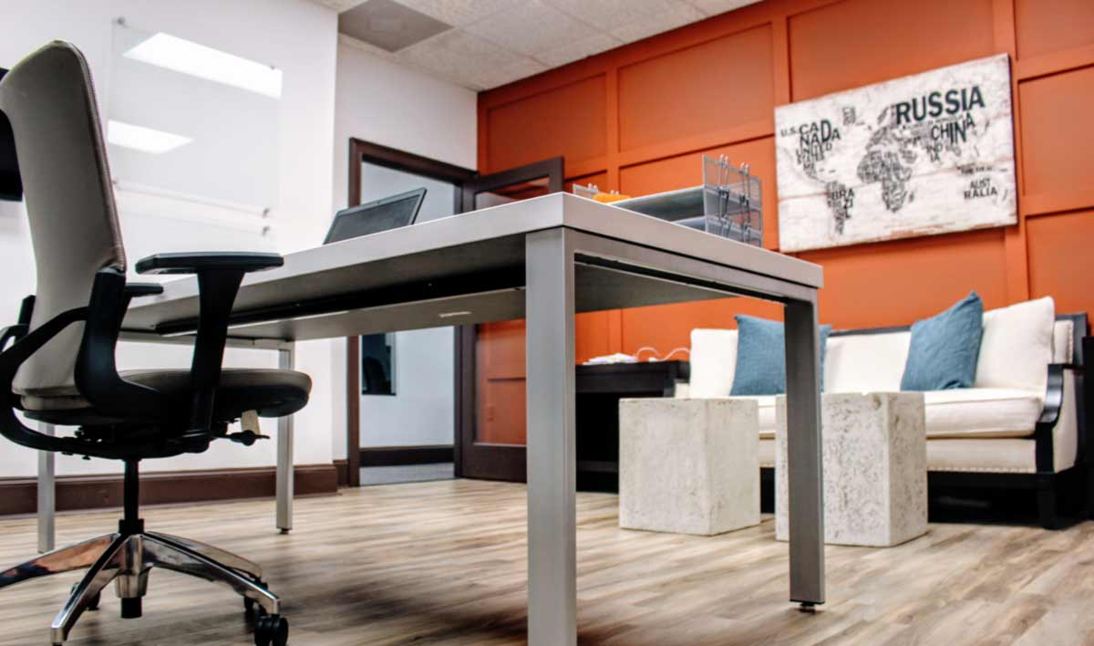Interior of Atlanta Exec Suite's office space ready for a business owner to work.  Modern furniture with clean lines, high ceilings, and artwork.